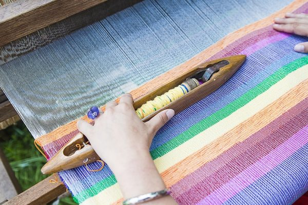 A-woman-weaving-rainbow-colored-cotton-cloth-on-a-loom