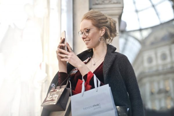 A2-woman-with-shopping-bags-looking-at-her-mobile-phone